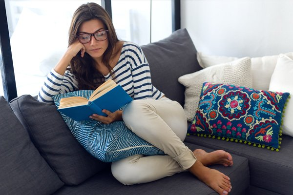 woman reading book with bifocals